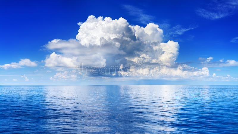 White cumulus clouds in blue sky over sea landscape, big cloud above ocean water panorama, horizon, beautiful tropical seascape. White cumulus clouds in blue sky stock photography