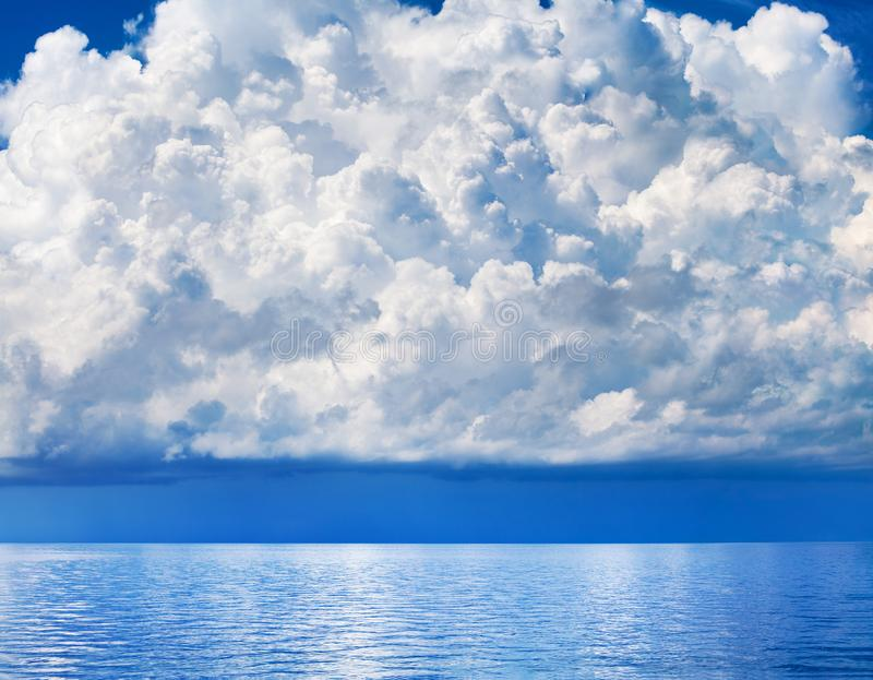 White cumulus clouds over sea close up blue sky background landscape, big fluffy cloud above ocean water panorama, cloudscape stock image