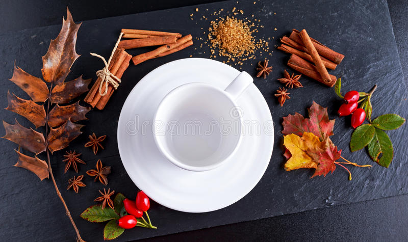 White cup with anis stars, brown sugar and cinnamon sticks on stone board autumn theme.  stock images