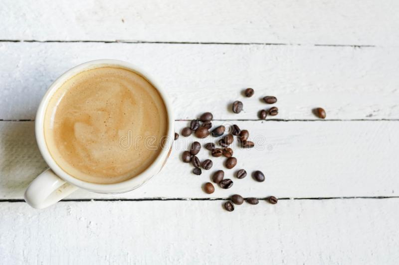 White cup of Black coffe with coffe beans and Copy Space on white wooden background royalty free stock photography