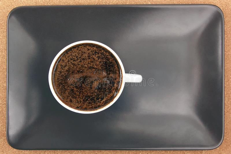 White cup of black coffee on a brown plate. hot drink stock photo