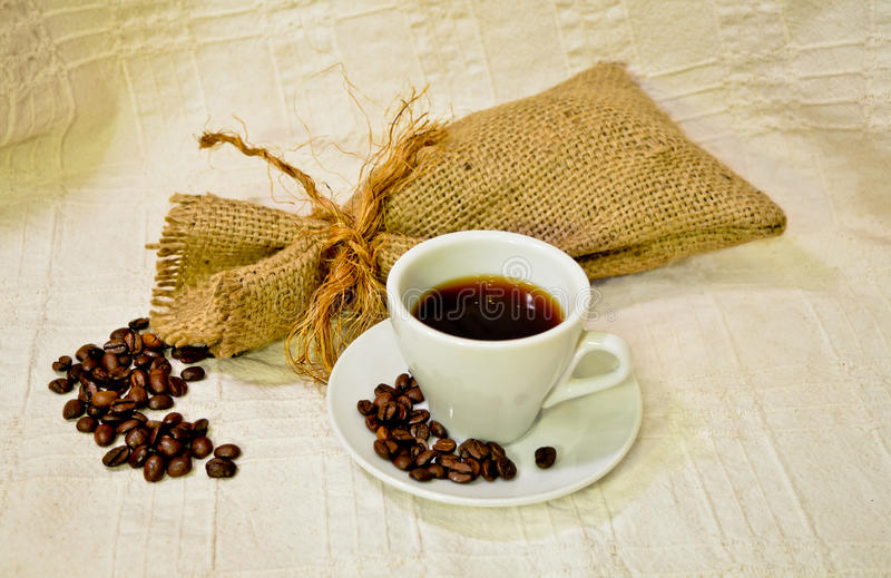 Cup of coffee with burlap sack of roasted coffee beans on the white linen table-cloth royalty free stock photo