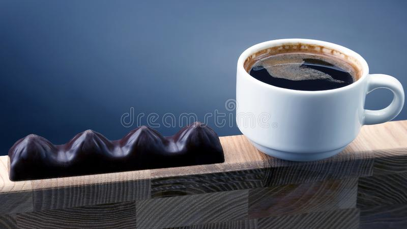 White Cup of black coffee with chocolate on a wooden frame stock photo