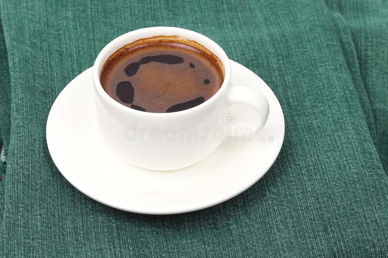 White Cup of black coffee rests on denim pants. Hot drink stock photography