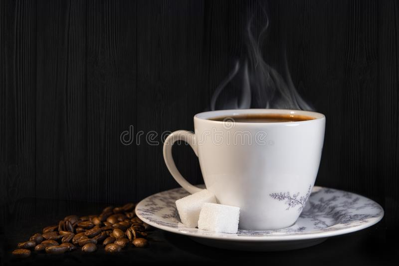 White cup with black coffee. With steam, on ebony background, coffee beans and two pieces of sugar royalty free stock photo
