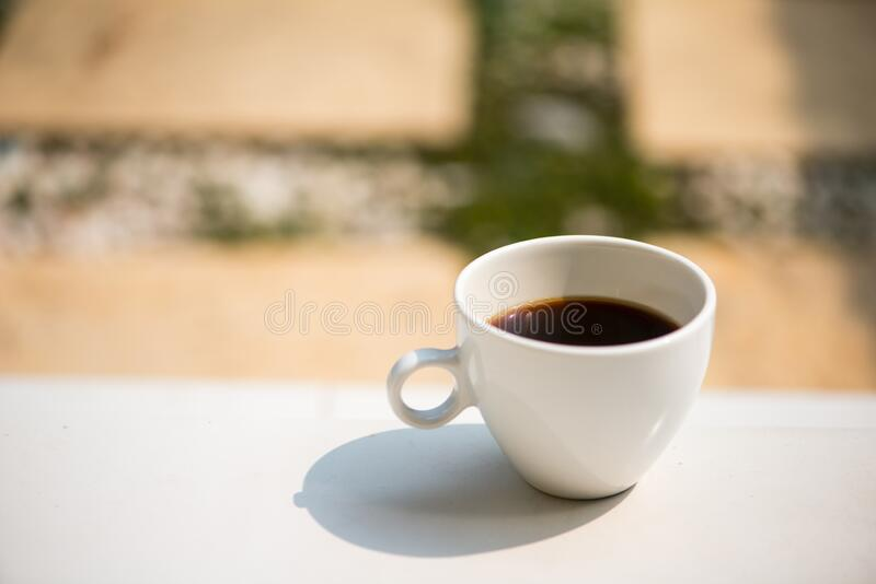 A white cup and black coffee on table. Show beverages background royalty free stock photo
