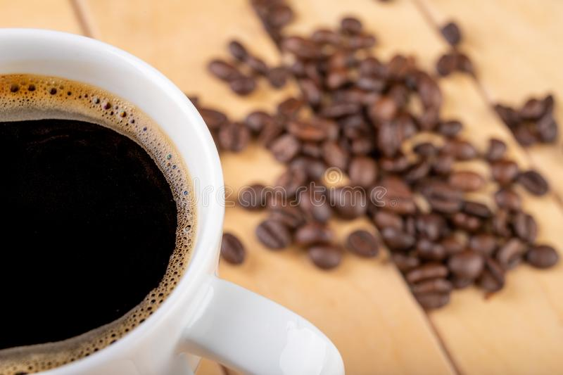 White cup with black coffee on a wooden table. A grain of coffee and a hot drink stock images