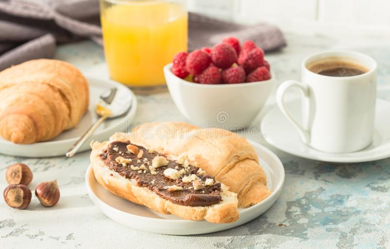 White cup of black tea with croissant or toasts with peanut butter, chokolate paste , jelly or jam on white wooden table, Breakfas royalty free stock image