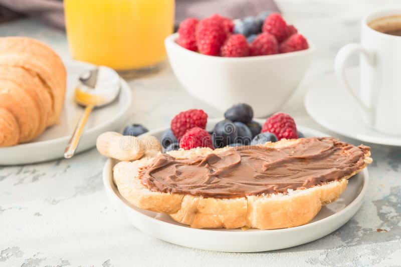 White cup of black tea with croissant or toasts with peanut butter, chokolate paste , jelly or jam on white wooden table, Breakfas stock photo