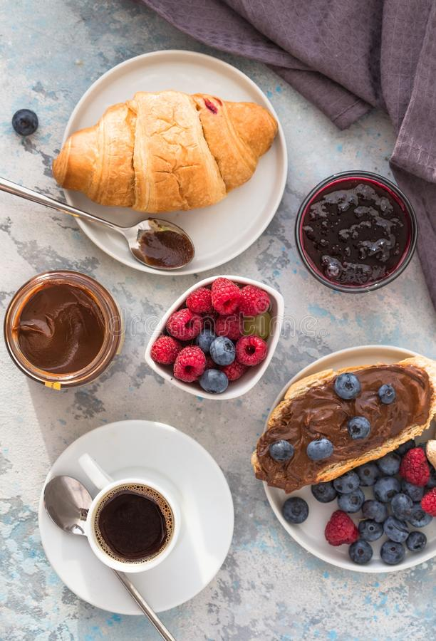 White cup of black tea with croissant or toasts with peanut butter, chokolate paste , jelly or jam on white wooden table, Breakfas stock photography