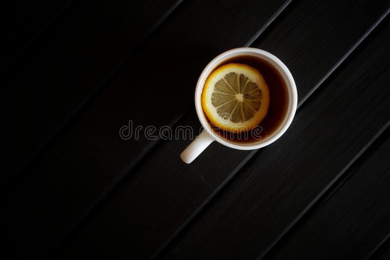 A white cup with black tea and a slice of lemon stands on a dark wooden table. View from above. Minimalism royalty free stock images