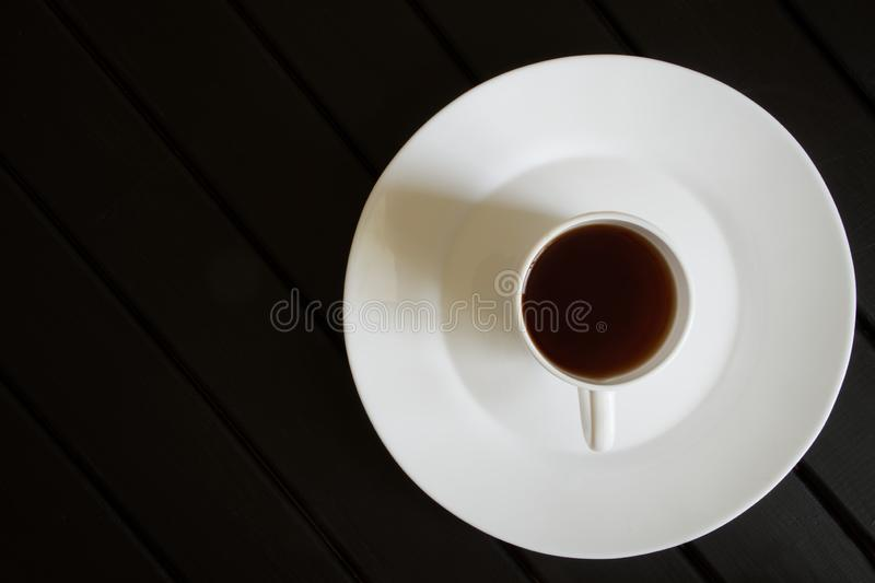 A white cup of black tea stands in a saucer on a dark wooden table. View from above. Minimalism royalty free stock image