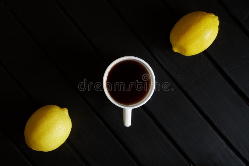 White cup with black tea and two yellow lemons on a dark wooden table. View from above. Minimalism royalty free stock image