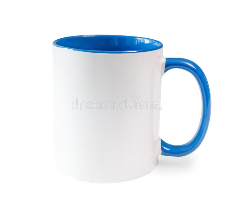 White cup with blue handle and inner surface. On a white table royalty free stock images