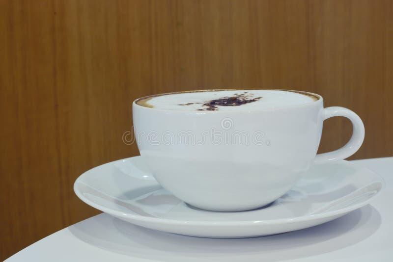 White cup cappuccino coffee on desk stock photo