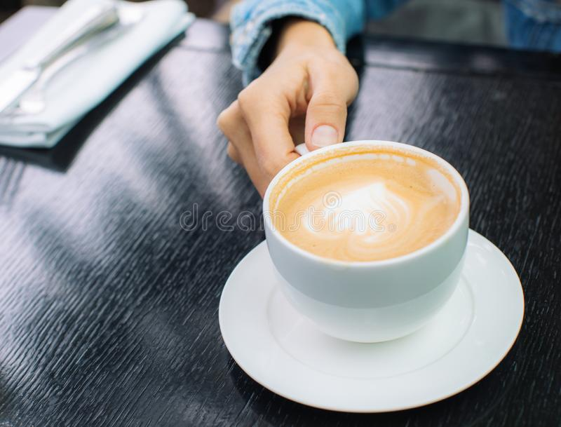 White Cup of cappuccino coffee with foam on the table in a cafe or restaurant with a shiny spoon in a woman`s hand royalty free stock photos