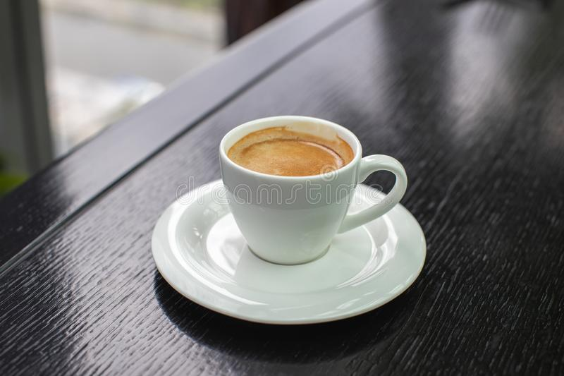 White Cup of cappuccino coffee with foam on the table in a cafe or restaurant royalty free stock photo