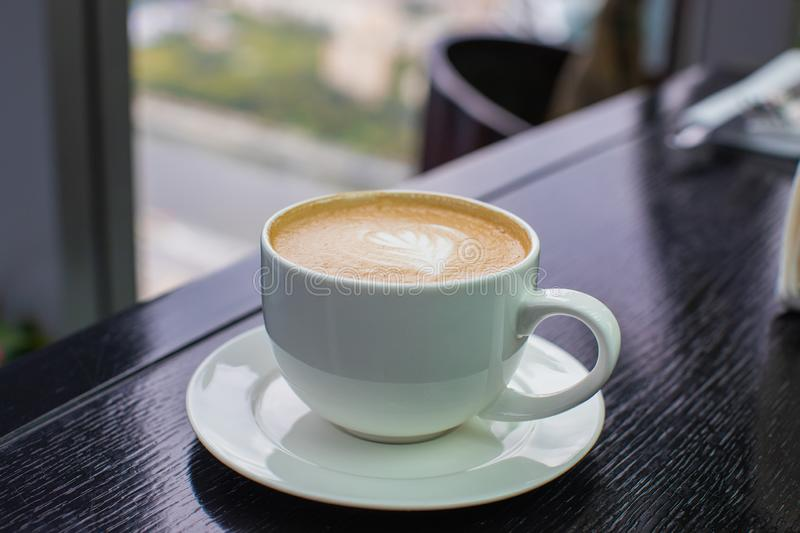 White Cup of cappuccino coffee with foam on the table in a cafe or restaurant stock photography