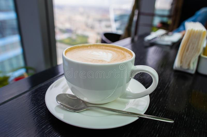 White Cup of cappuccino coffee with foam on the table in a cafe or restaurant with a shiny spoon stock photo
