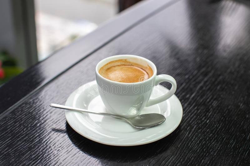 White Cup of cappuccino or expresso coffee with foam on the table in a cafe or restaurant with a shiny spoon royalty free stock image