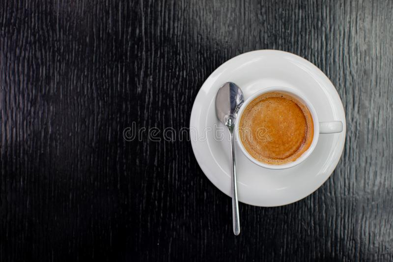 White Cup of cappuccino or expresso coffee with foam on the table in a cafe with a spoon stock image