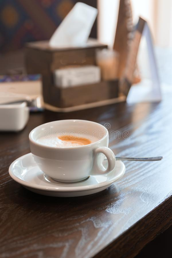White cup of cappuccino on wooden table in restaurant stylish toning stock photo