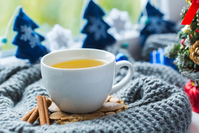 White cup of chamomile tea with grey scarf on the windowsill. Cup of tea with scarf and Christmas toys royalty free stock photo