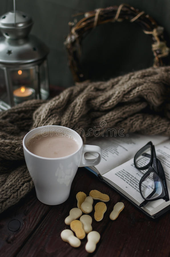 White cup of cocoa on an old wooden table with an entertaining b. Ook and reading glasses. Cozy life with cocoa, book holder and knit scarf royalty free stock photo