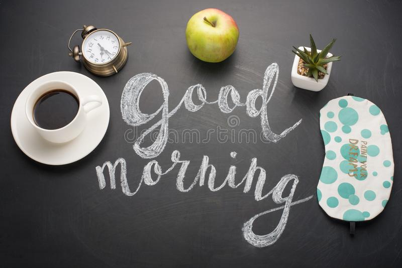 A white cup of coffee with an alarm clock and a good morning with a sleeping mask, an apple and a flower. Concept of a cheerful an. D kind morning royalty free stock photos