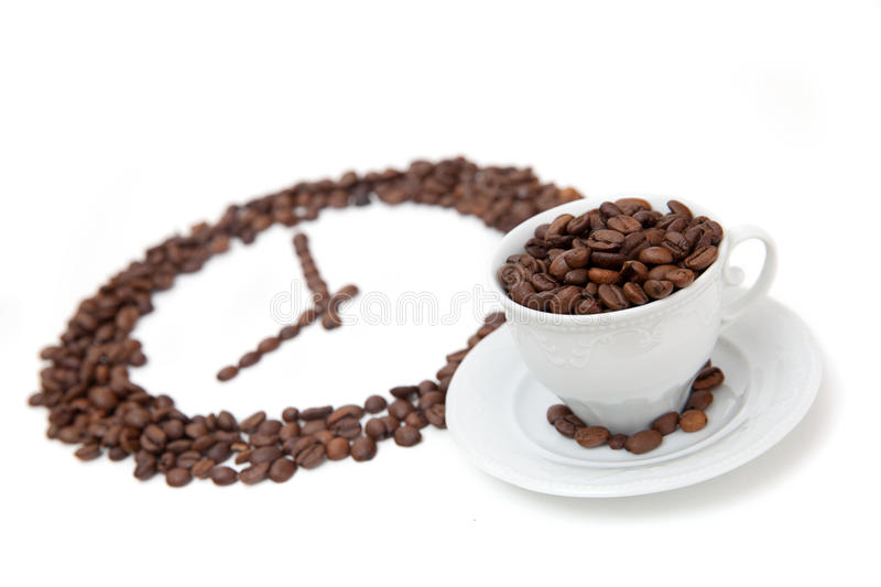 The white cup of coffee bean in front of grain clock stock images