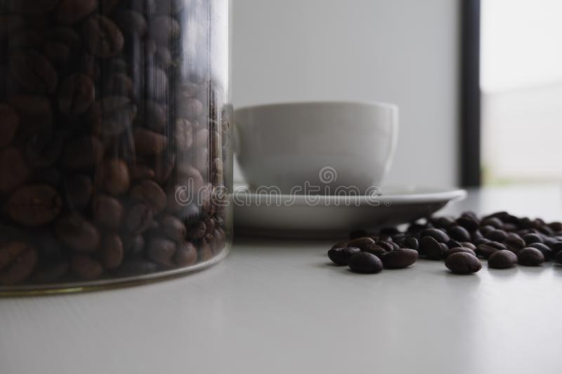 White cup and coffee bean in glass bottle stock photography
