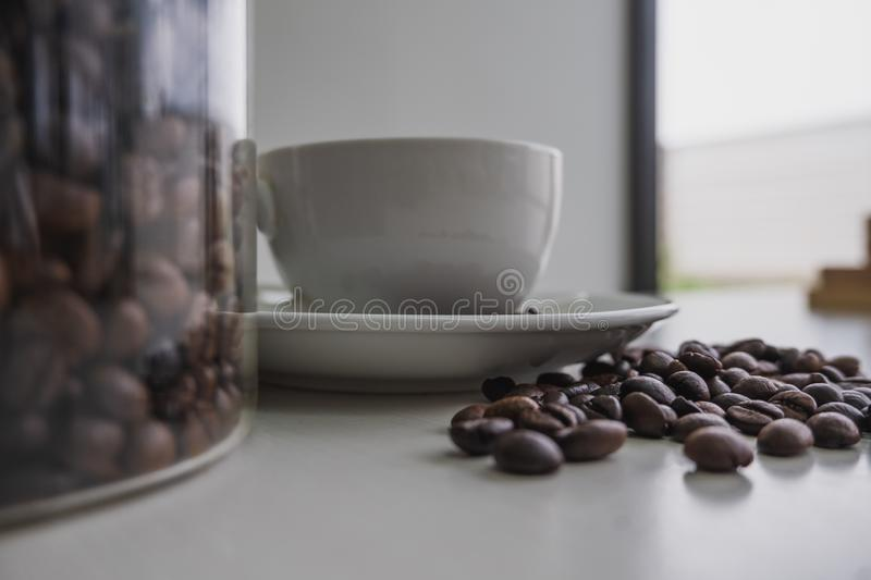 White cup and coffee bean in glass bottle stock images