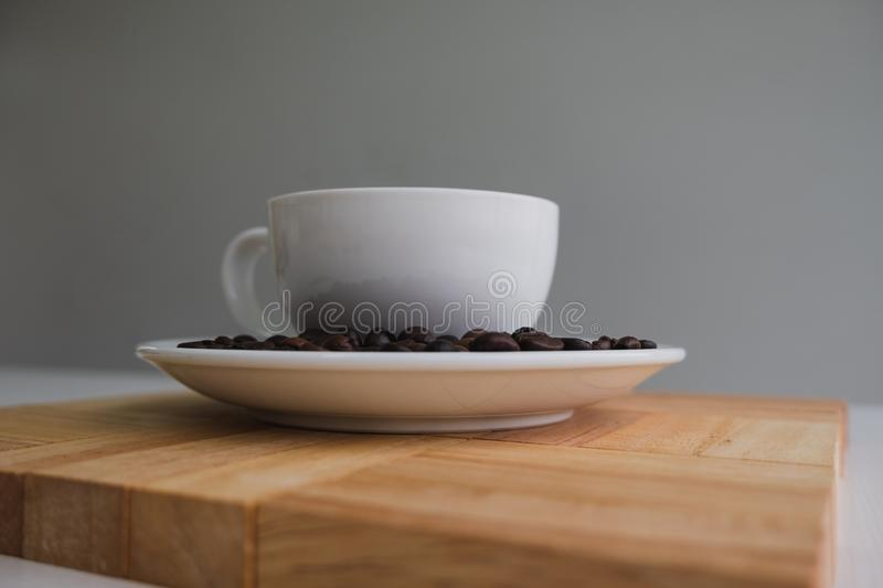White cup and coffee bean on wood block royalty free stock photos