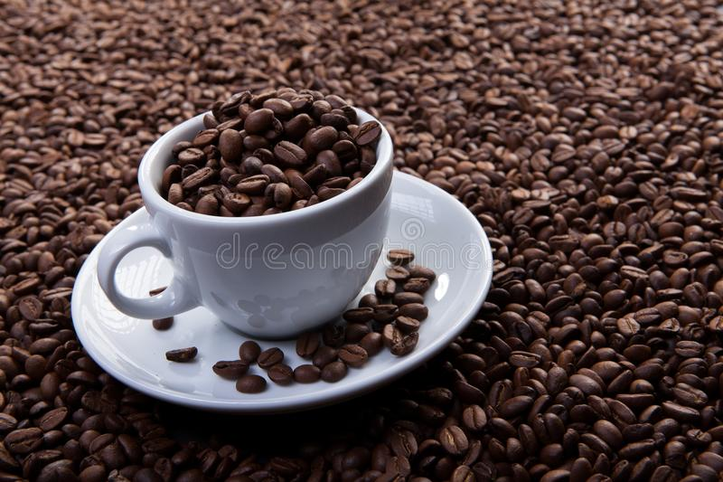 White cup of coffee at coffee beans backgrounds stock photography