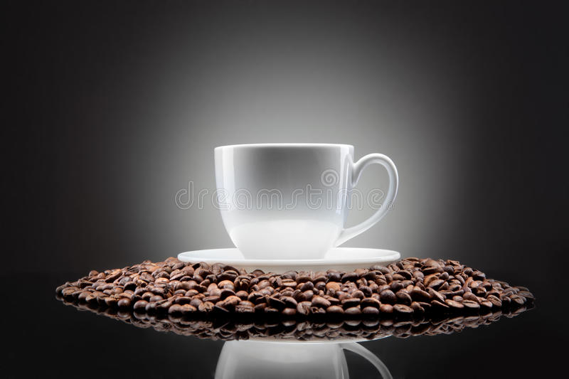 White cup with coffee beans on black royalty free stock images