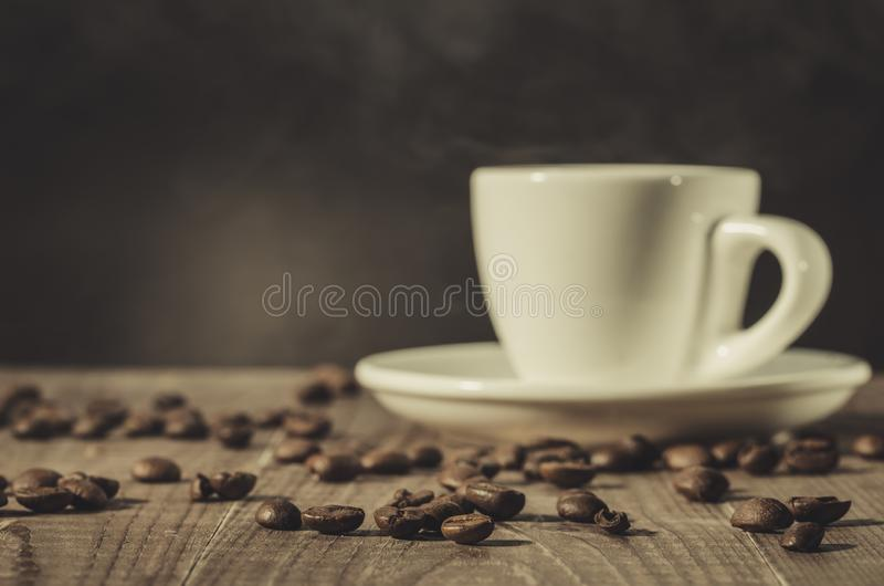 White cup of coffee and coffee beans on a dark wooden background/white cup of coffee and coffee beans on a dark wooden background royalty free stock photography