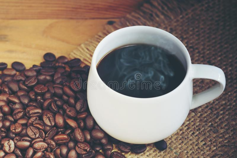 White cup of coffee with coffee bean stock photography