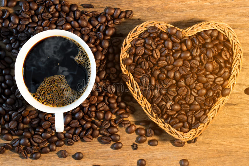 White cup of coffee and coffee bean on wood texture stock photo