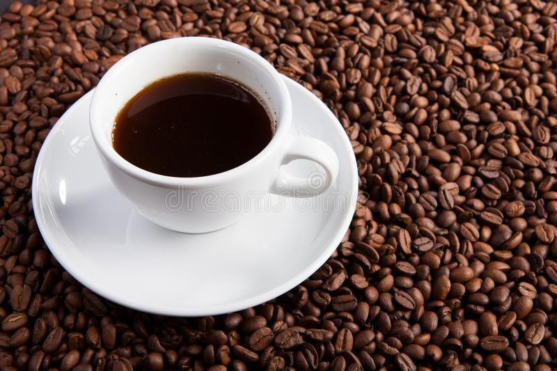 White cup of coffee at coffee beans backgrounds royalty free stock photo
