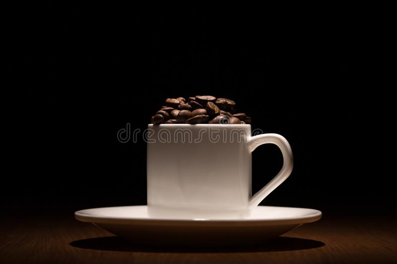 White cup of coffee with coffee beans, grains shoot in studio on stock photos
