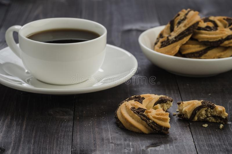 White cup of coffee and cookies/white cup of coffee and cookies on a wooden dark table stock photos