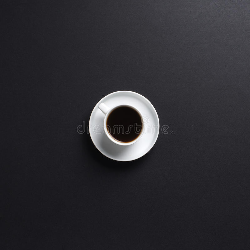 A white cup of coffee on a dark grey desk background stock image