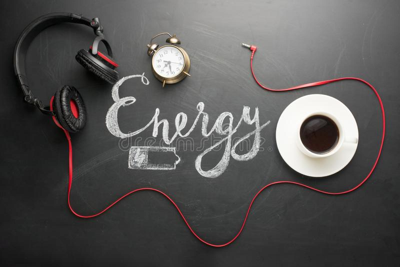 A white cup of coffee on a dark texture with an inscription of energy and a battery and an utterly alarm clock, and red headphones. ! The concept of an energetic stock photo