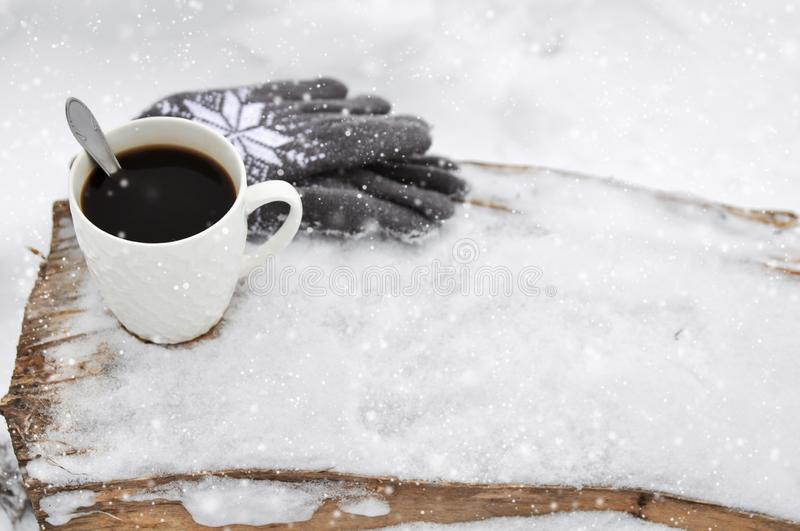 A white Cup of coffee and knitted gray gloves with a pattern on a wooden bench in the snow during a snowfall. Cozy stock photo
