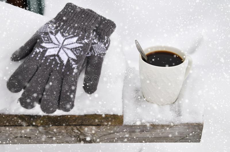 A white Cup of coffee and knitted gray gloves with a pattern on a wooden bench in the snow during a snowfall. Cozy stock photos