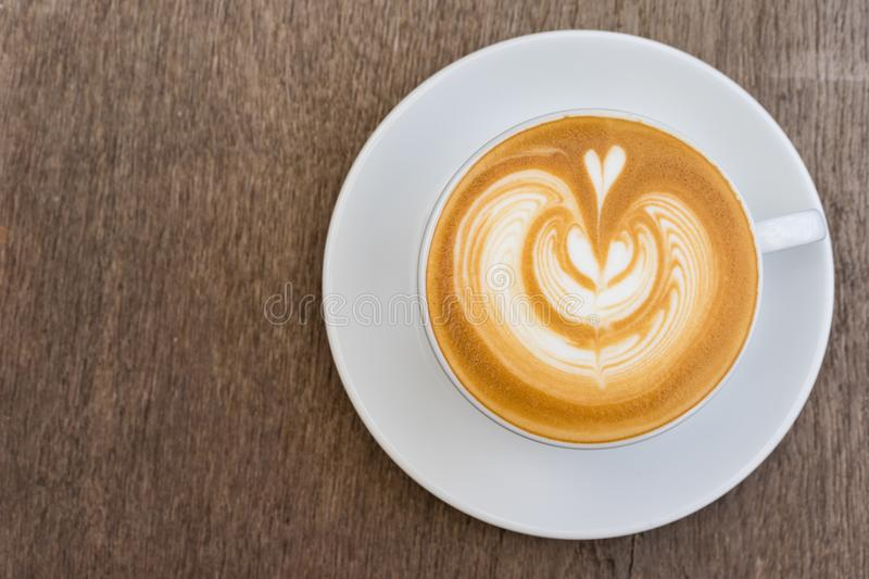 A white cup of coffee latte art on wood table stock photos