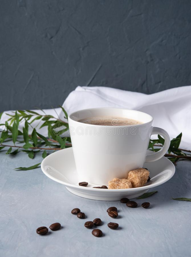 White cup of coffee latte with brown sugar and beans gray background stock photo