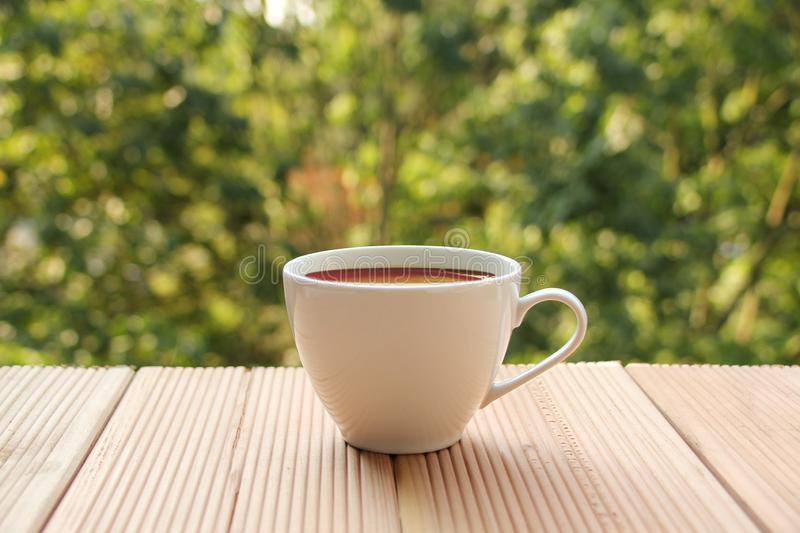 White cup with coffee on a light wooden table against a green summer garden, close-up, copy space royalty free stock photography