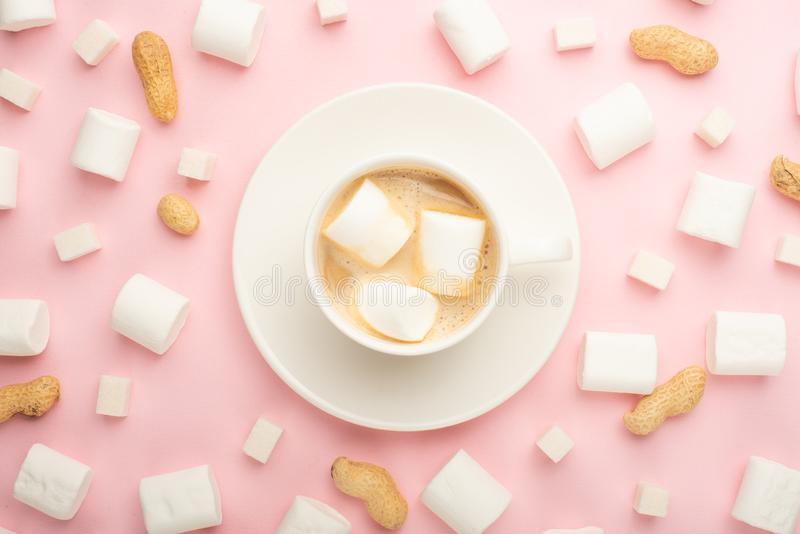 White cup of coffee with marshmallows, and marshmallows, and cubes of sugar, and nuts around on a pink background. Possibility to royalty free stock photo