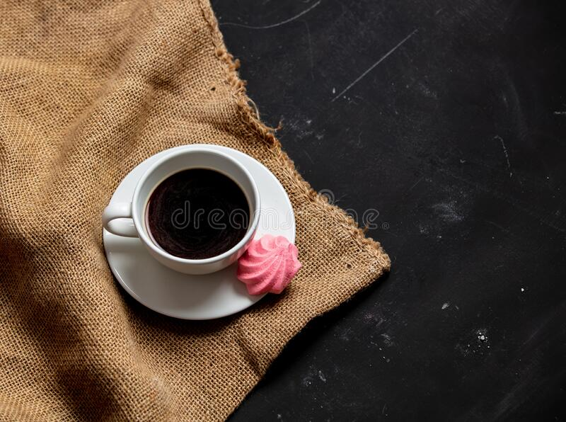 White cup of coffee and meringue on dark background royalty free stock image